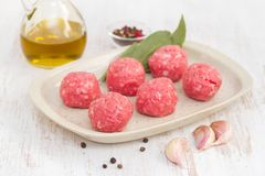Raw meatballs on the dish on wooden background. Raw meatballs on the dish on white wooden background Stock Photography