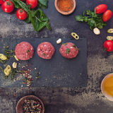 Raw meatballs and ingredients. Minced meat mixture for meatballs and ingredients on dark background. Top view, vintage toned image, blank space Stock Image