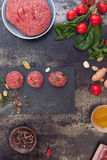Raw meatballs and meatball ingredients. Minced meat mixture for meatballs and ingredients on dark background. Top view, vintage toned image, blank space Royalty Free Stock Photo