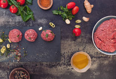 Raw meatballs and meatball ingredients. Minced meat mixture for meatballs and ingredients on dark background. Top view, vintage toned image, blank space Royalty Free Stock Images