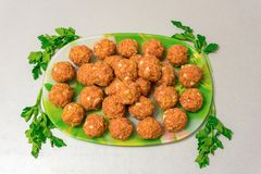 Raw meatballs on a platter. On the table Stock Image