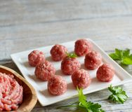 Raw  meatballs are ready to cook. On a plate Stock Photo