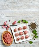 Raw  meatballs are ready to cook. Raw  meatballs with vegetables and herbs on a table Stock Photos