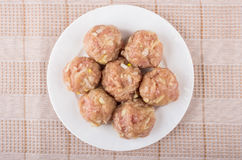 Raw meatballs in white plate on pink tablecloth Stock Images