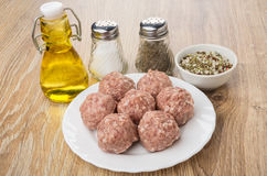 Raw meatballs in white plate, salt, pepper, spices and oil Royalty Free Stock Photography