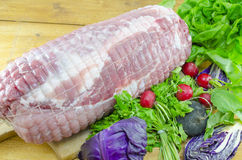Raw meatloaf on a cutting board. Decorated with red radishes, lettuce and cabbage Royalty Free Stock Image