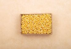 Raw millet in carton and on brown background stock photo