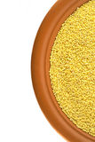 Raw millet on ceramic plate Royalty Free Stock Photography