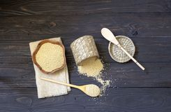 The raw millet on a wooden table. Ingredients for cooking. Raw millet in a bamboo box and a bowl on a wooden table close-up royalty free stock photo