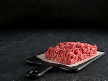 Raw minced beef on light gray cement background. Fresh raw minced beef on backing paper and cutting board over black cement background with copy space Royalty Free Stock Photo