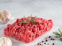 Raw minced beef on light gray cement background. Fresh raw minced beef on backing paper over light gray cement background with copy space royalty free stock photography