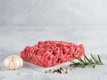 Raw minced beef on light gray cement background. Fresh raw minced beef on backing paper over light gray cement background with copy space Stock Photography
