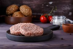Raw minced beef meat burger cutlets on dark wooden background royalty free stock photography