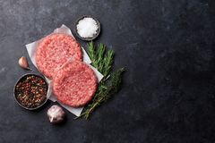 Raw minced beef meat for home made burgers. Raw minced meat and ingredients for home made grill burgers cooking with spaces and herbs. Top view with space for Royalty Free Stock Photography