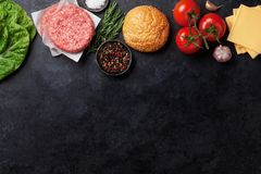 Raw minced beef meat and ingredients for burgers. Raw minced beef meat and ingredients for home made grill burgers cooking with spaces and herbs. Top view with Stock Photos