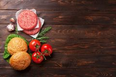 Raw minced beef meat and ingredients for burgers. Raw minced beef meat and ingredients for home made grill burgers cooking with spaces and herbs. Top view with Stock Images