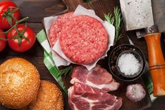 Raw minced beef meat and ingredients for burgers. Raw minced beef meat and ingredients for home made grill burgers cooking with spaces and herbs. Top view Stock Images