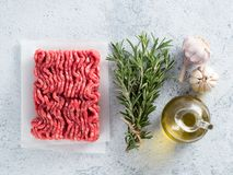 Raw minced beef, rosemary, olive oil. top view. Fresh raw minced beef, fresh rosemary, garlic, olive oil on backing paper over light gray cement background. Top Stock Photography