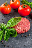 Raw minced beef steak burger. Fresh raw home-made minced beef steak burger with spices, tomatoes and basil, on a stone table, copy space, close view Stock Photo