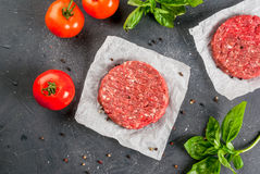 Raw minced beef steak burger. Fresh raw home-made minced beef steak burger with spices, tomatoes and basil, on a stone table, copy space, top view Royalty Free Stock Photos