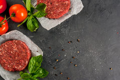 Raw minced beef steak burger. Fresh raw home-made minced beef steak burger with spices, tomatoes and basil, on a stone table, copy space, top view Stock Image