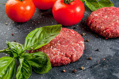 Raw minced beef steak burger. Fresh raw home-made minced beef steak burger with spices, tomatoes and basil, on a stone table, copy space, top view Stock Photo