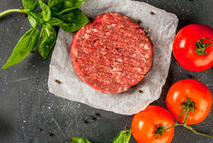 Raw minced beef steak burger. Fresh raw home-made minced beef steak burger with spices, tomatoes and basil, on a stone table, copy space, top view Stock Images