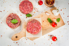 Raw minced beef steak burger. Fresh raw home-made minced beef steak burger with spices, tomatoes and basil, on a white stone concrete table Royalty Free Stock Image
