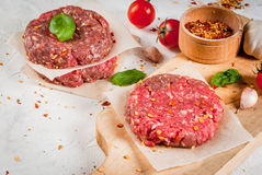 Raw minced beef steak burger. Fresh raw home-made minced beef steak burger with spices, tomatoes and basil, on a white stone concrete table Royalty Free Stock Images