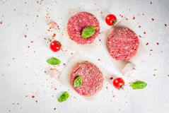 Raw minced beef steak burger. Fresh raw home-made minced beef steak burger with spices, tomatoes and basil, on a white stone concrete table, copy space, top view Stock Image