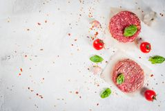 Raw minced beef steak burger. Fresh raw home-made minced beef steak burger with spices, tomatoes and basil, on a white stone concrete table, copy space, top view Royalty Free Stock Image