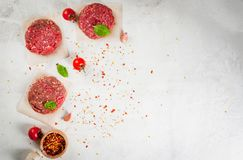 Raw minced beef steak burger. Fresh raw home-made minced beef steak burger with spices, tomatoes and basil, on a white stone concrete table, copy space, top view Royalty Free Stock Photography