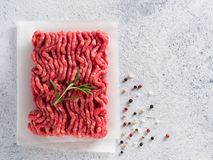 Raw minced beef top view copy space. Fresh raw minced beef on backing paper over light gray cement background with copy space. Top view or flat-lay Royalty Free Stock Photos
