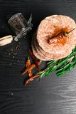 Raw Minced burger Meat with Herb and Spice Prepared for Grilling with rosemary, hot red chili, black pepper. On black wooden table royalty free stock photo