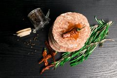 Raw Minced burger Meat with Herb and Spice Prepared for Grilling with rosemary, hot red chili, black pepper. On black wooden table stock photography