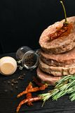 Raw Minced burger Meat with Herb and Spice Prepared for Grilling with rosemary, hot red chili, black pepper. On black wooden table stock photo