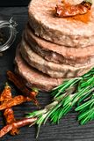 Raw Minced burger Meat with Herb and Spice Prepared for Grilling with rosemary, hot red chili, black pepper. On black wooden table stock images