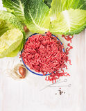 Raw minced meat and cabbage leaves on white wooden background. Top view Royalty Free Stock Photos