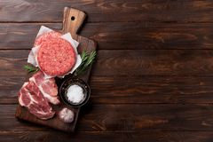 Raw minced meat cooking. Raw minced meat and ingredients for home made grill burgers cooking with spaces and herbs. Top view with space for your text Royalty Free Stock Image