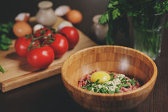 Raw minced meat with egg, herbs and fresh tomatoes on wooden table. Ingredients for cooking meat balls or loaf. In rustic kitchen Royalty Free Stock Photos