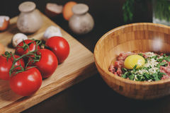 Raw minced meat with egg, herbs and fresh tomatoes on wooden table. Ingredients for cooking meat balls or loaf. In rustic kitchen Stock Photo
