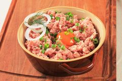 Raw minced meat. And egg yolk in a ceramic pot Royalty Free Stock Images