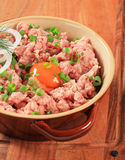 Raw minced meat. And egg yolk in a ceramic pot Stock Photos