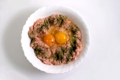 Raw minced meat and eggs. Overhead view of bowl of raw minced meat wit herbs and two raw eggs; isolated on white studio background royalty free stock images