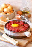 Raw minced meat, eggs, olive oil and onions Royalty Free Stock Photos