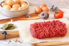 Raw minced meat, eggs, tomato and onions Stock Photo