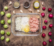Raw minced meat with flour and onions in a glass bowl with herbs, sprouts and radish on wooden rustic background top view close up. Raw minced meat with flour Stock Photo
