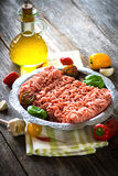 Raw minced meat. Fresh raw minced meat in a plate close up on a rustic wooden table Royalty Free Stock Photos