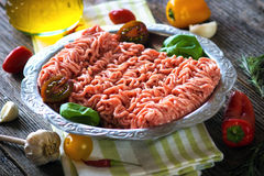 Raw minced meat. Fresh raw minced meat in a plate close up on a rustic wooden table Stock Photo