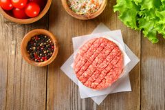 Raw minced meat for home made grill burgers cooking with spaces and herbs. Raw minced meat for home made grill burgers cooking with spaces and herbs royalty free stock image